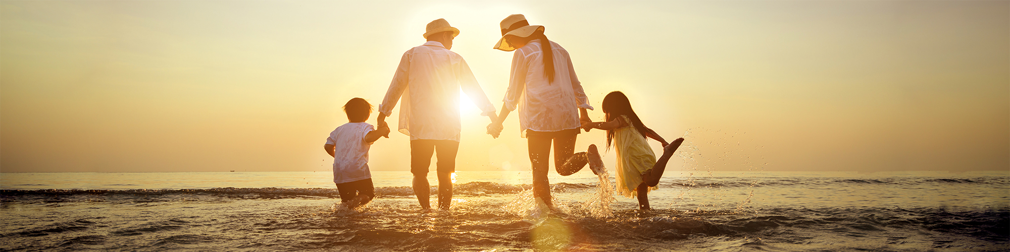 Family holds hands while watching the sunset at the beach